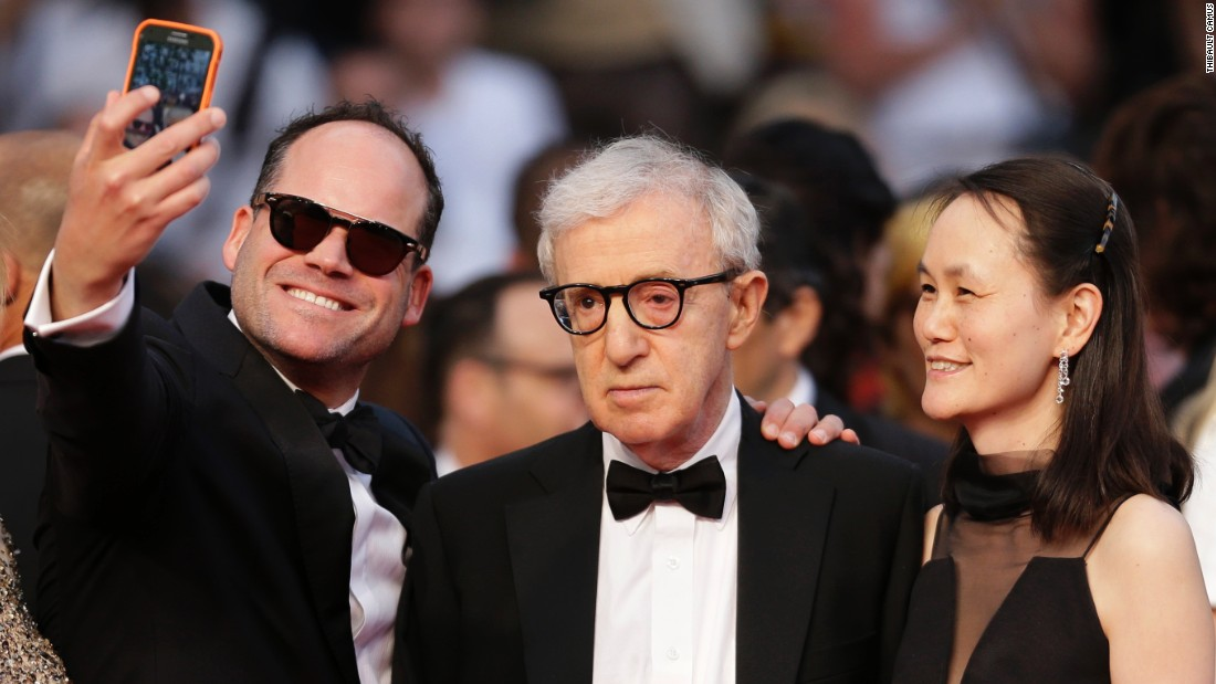 Film director Woody Allen, center, appears less than enthused as a man takes a selfie at the Cannes Film Festival on Friday, May 15. At right is Allen's wife, Soon-Yi Previn.