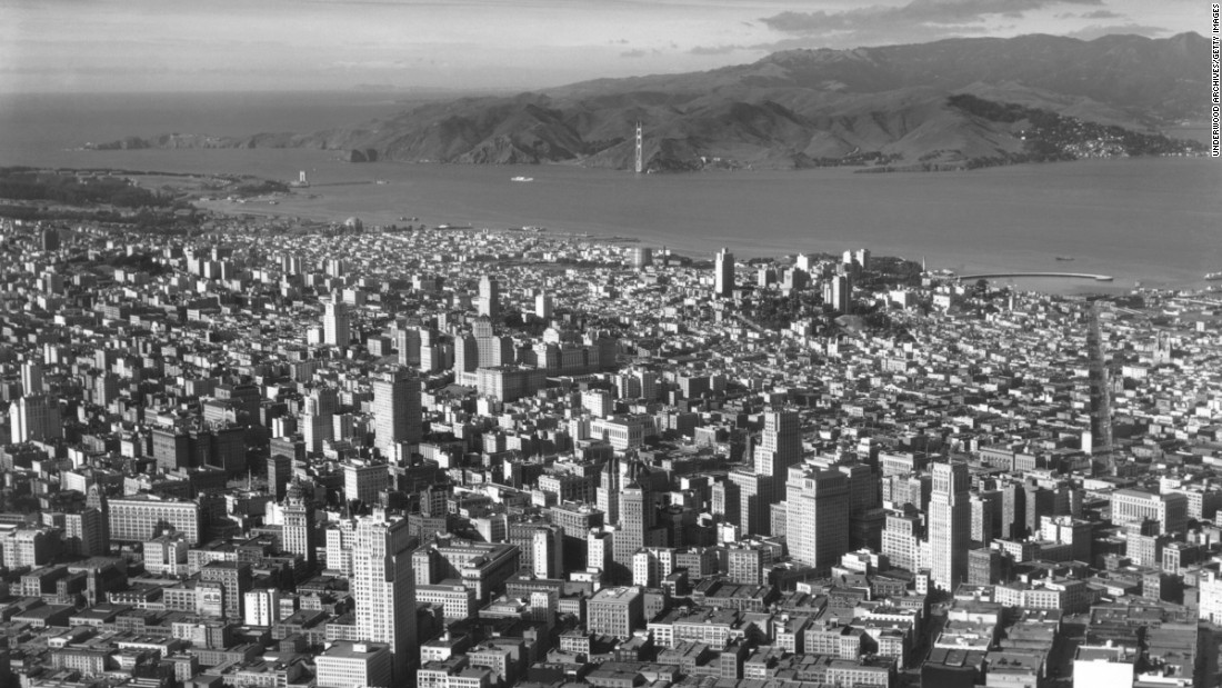 This aerial image from 1934 shows downtown San Francisco and construction of the Golden Gate Bridge in the background. The bridge's north Marin Tower is nearly completed, although the southern one had yet to be erected.
