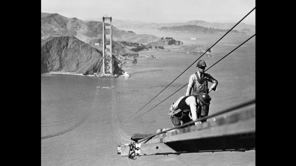 Bridge workers build a catwalk that connects the towers at both sides of the strait so they can attach the suspension cables to hold up the bridge. Workers on the bridge were buffeted by high winds and faced constant fears of plummeting to their deaths.