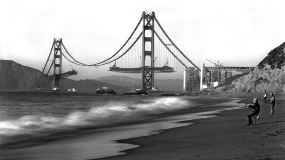 """Fishermen on Baker Beach enjoy the view of the Golden Gate Bridge under construction. Work on the bridge began on January 5, 1933, and lasted four years and four months. The span is painted a distinctive color named """"international orange."""""""