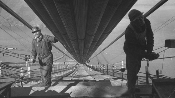 Two workmen add the last strands to one of the two enormous cables that run between the towers and support the six-lane highway below. Construction of the bridge cost $35 million; engineers estimate that if it was built today, the bridge would cost more than $1.3 billion.