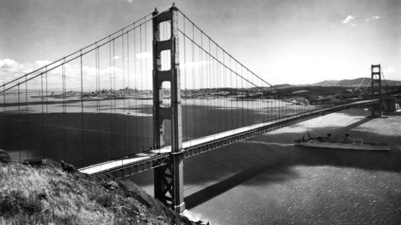 """A Matson Liner passes under the Golden Gate Bridge on its way out to sea in the late 1930s. The American Society of Civil Engineers named the bridge one of the """"Wonders of the Modern World."""" Since its completion, the bridge has been crossed by more than 2 billion vehicles and closed because of weather conditions only three times."""