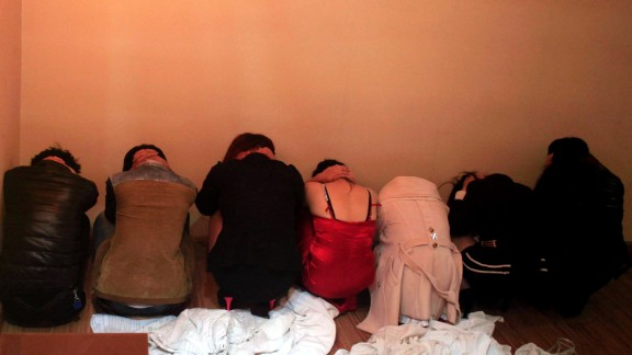This picture taken on February 9, 2014 shows workers crouching by a wall during a police raid on an entertainment center in Dongguan. An exposé by China's state broadcaster on rampant prostitution in the country's 'sex capital' Dongguan triggered a huge police operation.