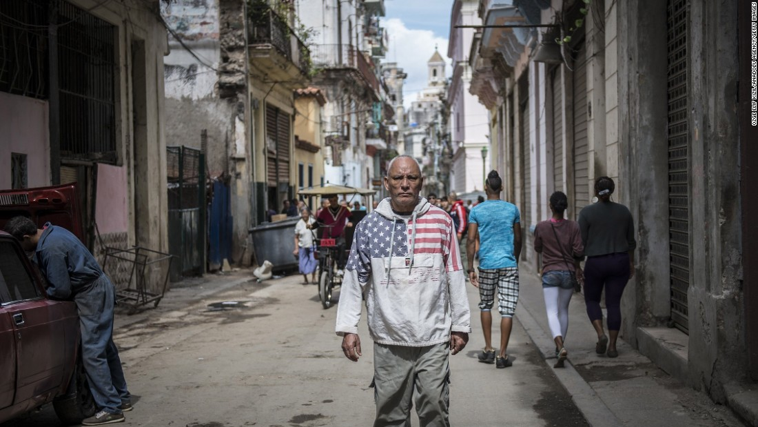 A man wearing an American flag sweatshirt walks through a street in Havana in February.