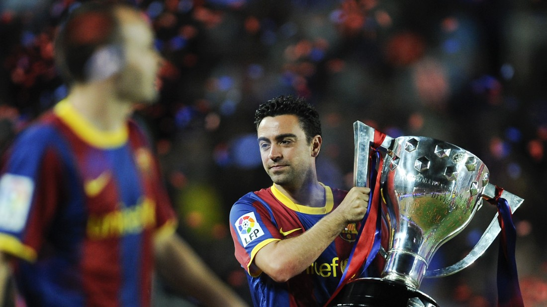 Xavi holds aloft the Spanish league trophy -- he won it eight times with Barcelona.
