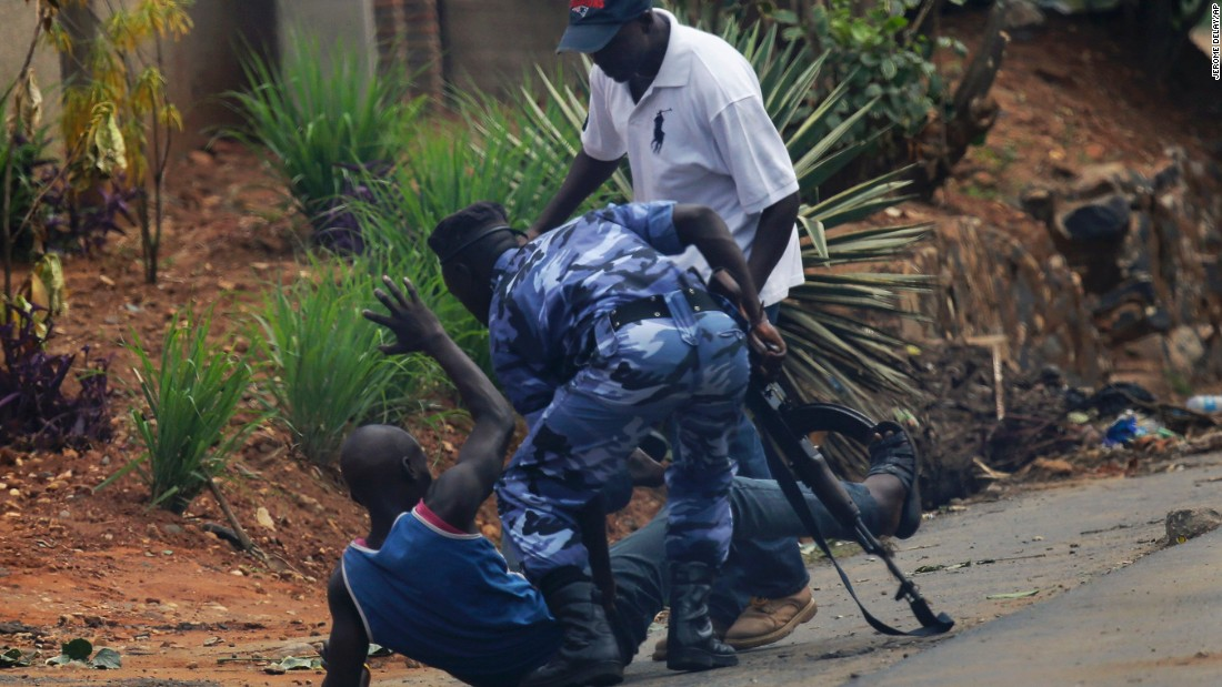 A police officer and a plainclothes member of the Intelligence Services kick a protester in Bujumbura on May 20.