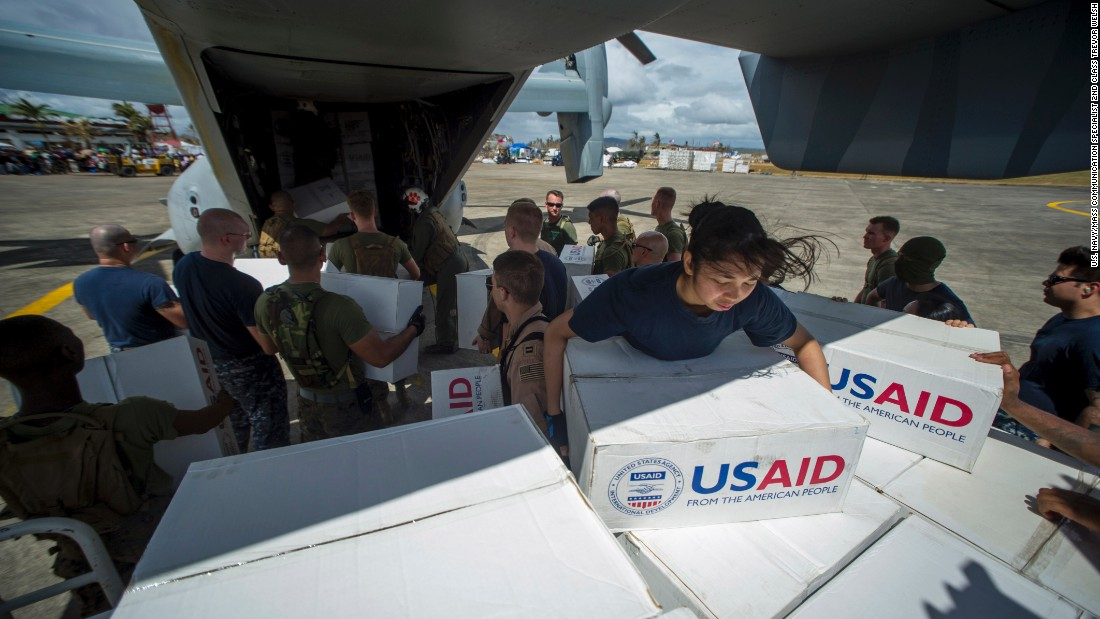 Sailors assigned to the aircraft carrier USS George Washington (CVN 73) and Marines assigned to the 3d Marine Expeditionary Brigade load boxes of supplies into a U.S. Marine Corps MV-22 Osprey from Marine Medium Tiltrotor Squadron (VMM) 262 to be airlifted to nearby villages during relief efforts after Supertyphoon Haiyan.