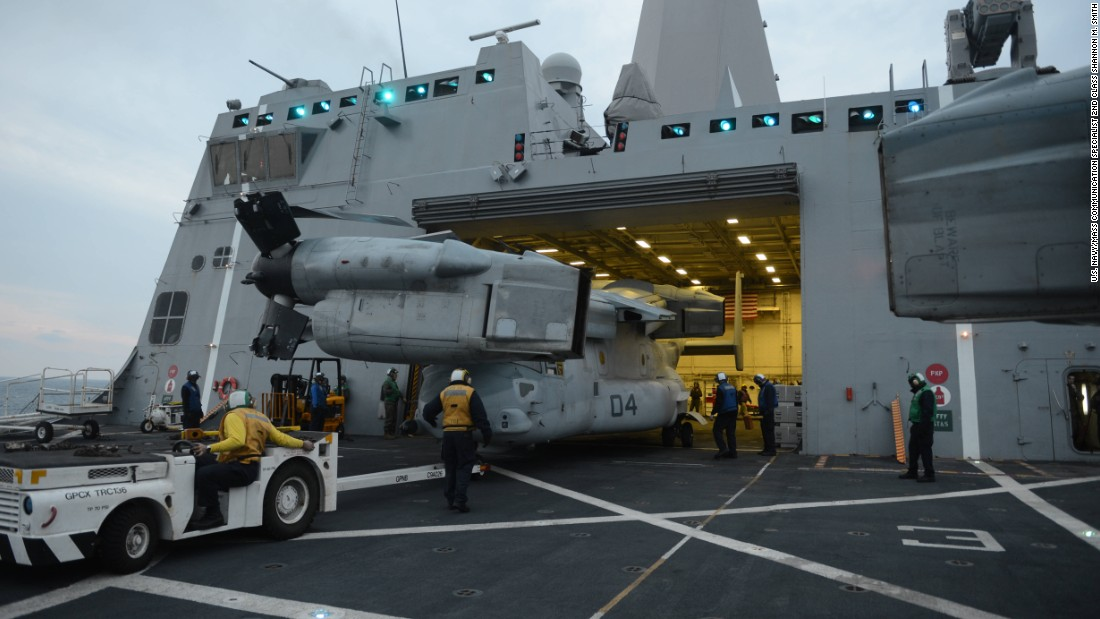 Sailors aboard the amphibious transport dock ship USS Mesa Verde (LPD 19) stow an MV-22 Osprey in the hangar bay.