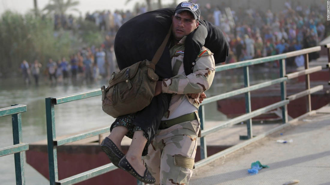 "An Iraqi soldier helps a displaced woman cross a bridge on the outskirts of Baghdad, Iraq, on Tuesday, May 19. The ISIS militant group <a href=""http://www.cnn.com/2015/05/17/asia/isis-ramadi/index.html"" target=""_blank"">recently took control of the nearby city of Ramadi, </a>the largest city in western Iraq."