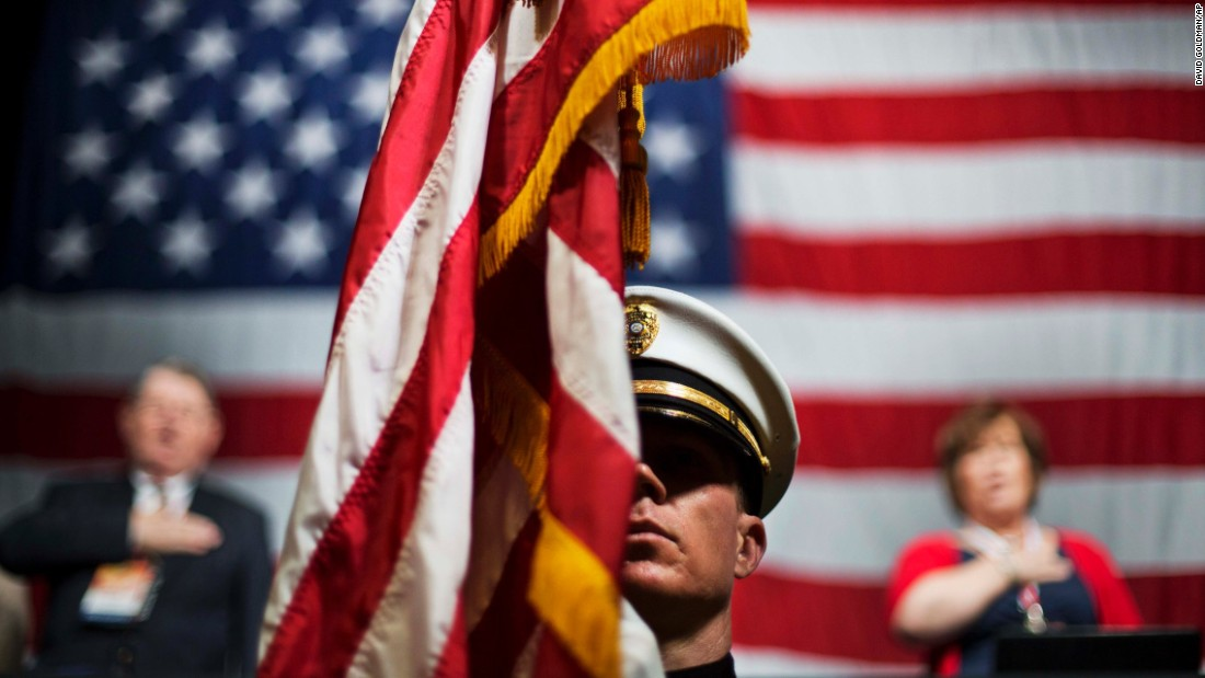 Officer Chris Armel of the Athens-Clarke County Police Department holds an American flag while the Pledge of Allegiance is recited Friday, May 15, at the Georgia Republican Convention in Athens, Georgia.