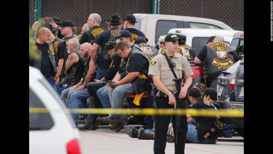 "A McLennan County deputy stands guard near a group of bikers in Waco, Texas, after <a href=""http://www.cnn.com/2015/05/17/us/gallery/waco-shooting-twin-peaks/index.html"" target=""_blank"">a fight between rival gangs</a> left at least nine people dead on Sunday, May 17."