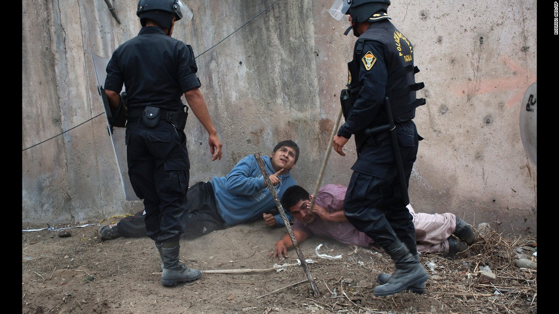 Riot police detain men during a land eviction in Lima, Peru, on Tuesday, May 19. Hundreds of people squatted on land that, according to the Ministry of Culture, is an archaeological site.