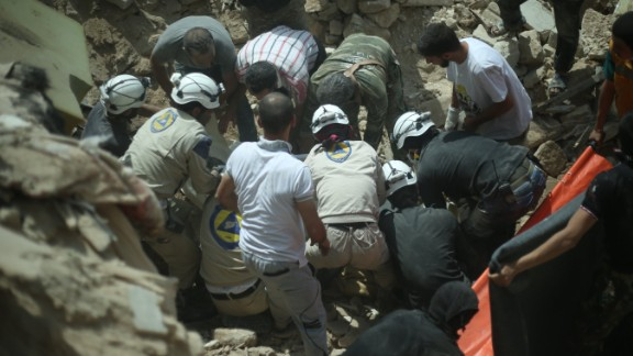 White Helmets assist in removing the body of a Syrian from the rubble of buildings following a reported barrel bomb attack by government forces on the Qadi Askar district of the northern Syrian city of Aleppo on May 20, 2015.