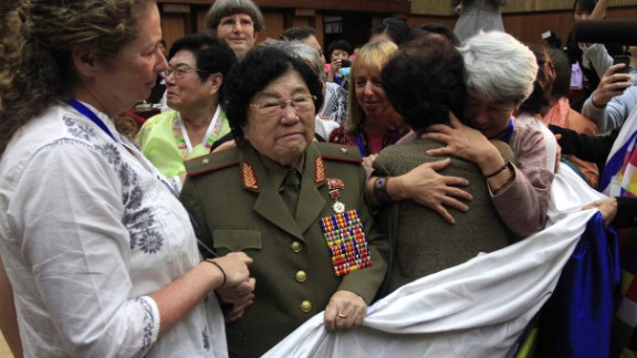 Documentary filmmaker Abigail Disney of the United States, left, shakes the hands of Jon Ku Gang, 68, second left, a North Korean woman who shared her experiences during the Korean War, at a meeting held at the People