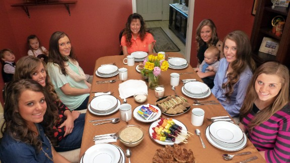 Michelle Duggar sits at the dinner table with other women and girls in the family.