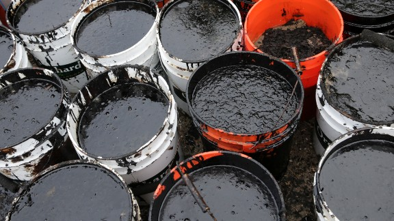 Plastic buckets are filled with oil collected from the beach on May 21.