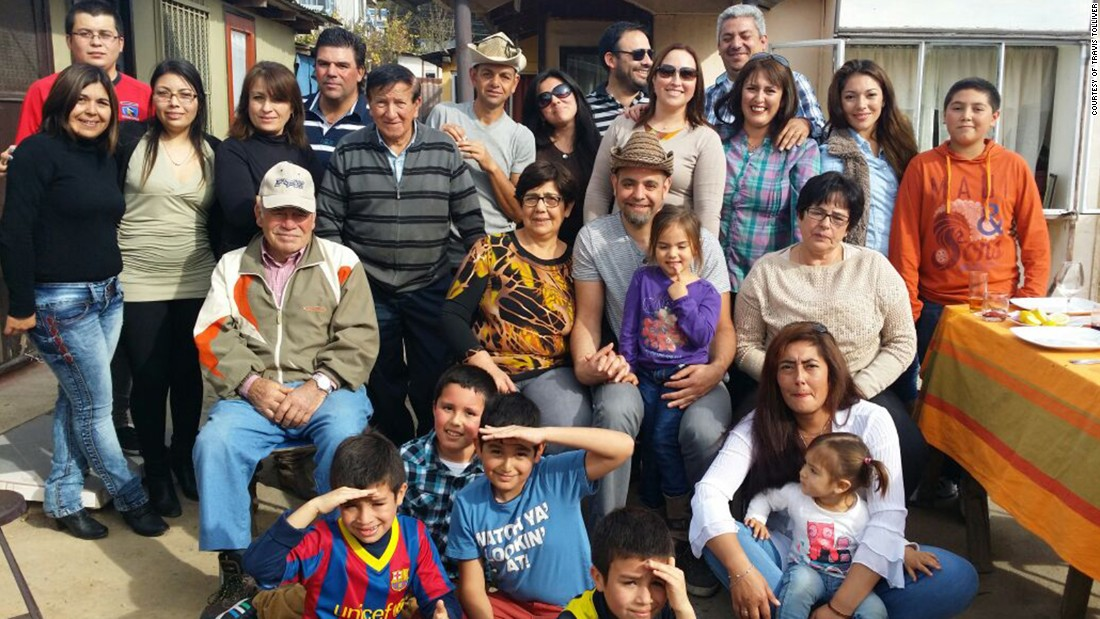 Travis Tolliver sits in the center surrounded by his biological family in Chile. He's wearing a hat and a young girl in a purple T-shirt sits on his lap.
