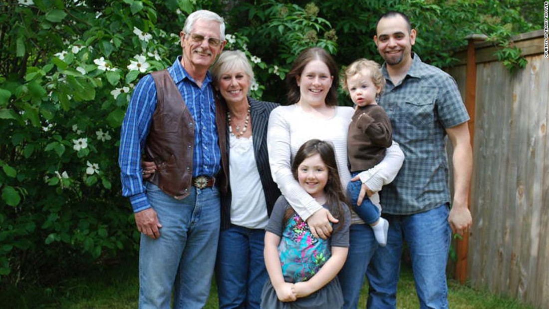 Travis Tolliver poses with his adoptive U.S. parents, his wife and their two children in 2010. His parents were told Travis was an abandoned baby.