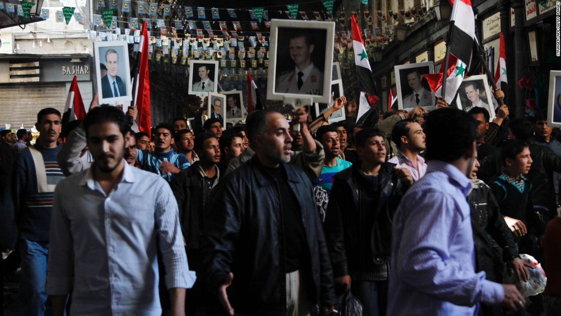 Pro-government protesters hold pictures of Syrian President Bashar al-Assad and his late father, Hafez al-Assad, during a rally in Damascus, Syria, on March 18, 2011. Bashar al-Assad has ruled Syria since 2000, when his father passed away following 30 years in charge. An anti-regime uprising that started in March 2011 has spiraled into civil war. The United Nations estimates more than 220,000 people have been killed.