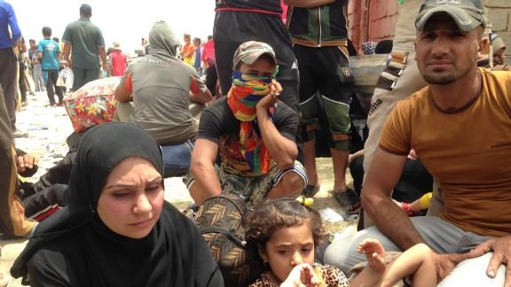 A family waits on the Bzebiz Bridge as they try to flee Iraq