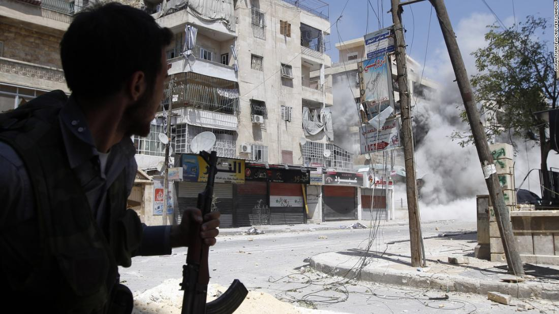 A Free Syrian Army fighter runs for cover as a Syrian Army tank shell hits a building across the street during clashes in the Salaheddine neighborhood of central Aleppo on August 17, 2012.
