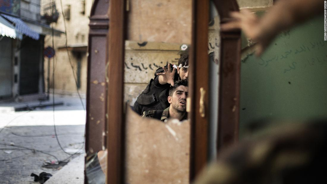 Free Syrian Army fighters are reflected in a mirror they use to see a Syrian Army post only 50 meters away in Aleppo on September 16, 2012.
