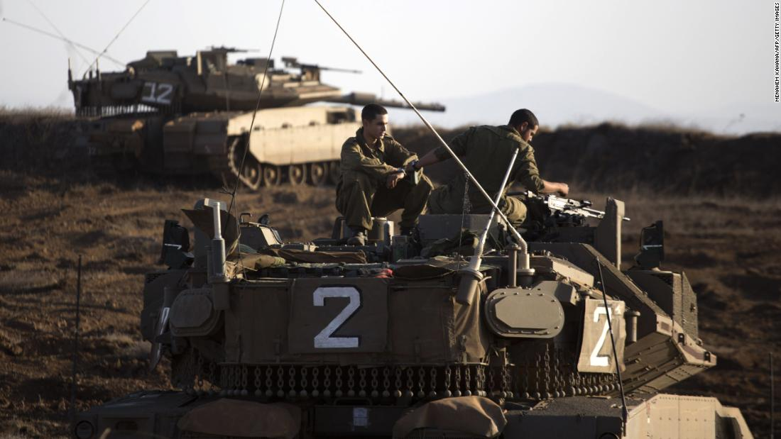 An Israeli tank crew sits on the Golan Heights overlooking the Syrian village of Breqa on November 6, 2012. Israel fired warning shots toward Syria after a mortar shell hit an Israeli military post. It was the first time Israel fired on Syria across the Golan Heights since the 1973 Yom Kippur War.