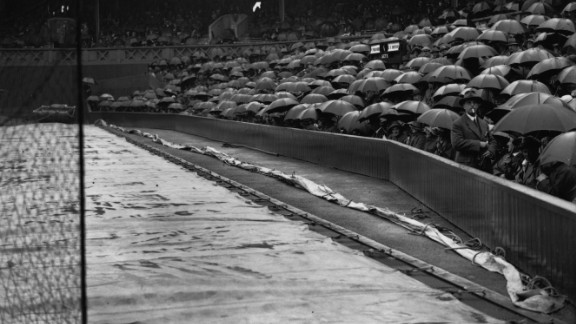 Some things never change -- the covers are on and the rain is falling. This example is on Centre Court during the 1922 tournament.