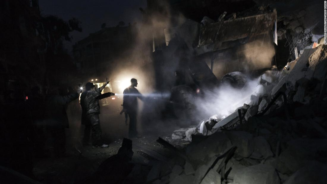 Syrians look for survivors amid the rubble of a building targeted by a missile in the al-Mashhad neighborhood of Aleppo on January 7, 2013.