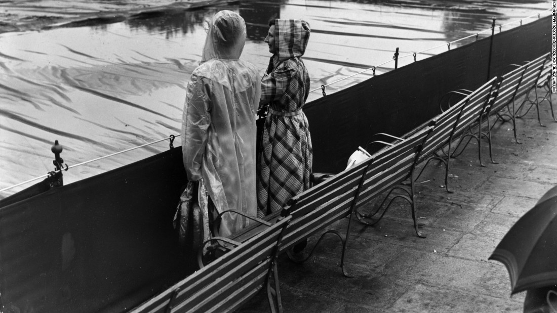 Two spectators gaze forlornly at flooded, covered Wimbledon courts in July 1950.