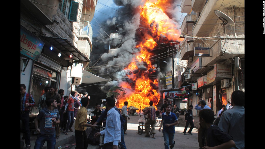 Residents run from a fire at a gasoline and oil shop in Aleppo's Bustan Al-Qasr neighborhood on October 20, 2013. Witnesses said the fire was caused by a bullet from a pro-government sniper.