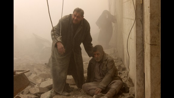 An injured man is helped following an airstrike in Aleppo