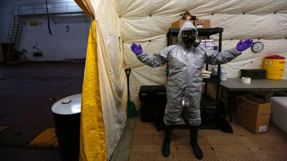 A US ship staff member wears personal protective equipment at a naval airbase in Rota, Spain, on April 10, 2014. A former container vessel was fitted out with at least  million of gear to let it take on about 560 metric tons of Syria's most dangerous chemical agents and sail them out to sea, officials said.