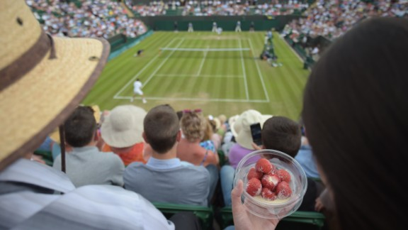 A spectator eats strawberries and cream as she watches Spain's David Ferrer play against Russia's Andrey Kuznetsov during the 2014 event.