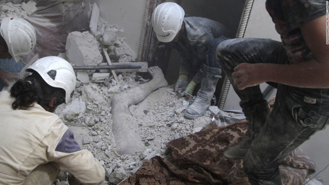 Volunteers remove a dead body from under debris after shelling in Aleppo on August 29, 2014. According to the Syrian Civil Defense, barrel bombs are now the greatest killer of civilians in many parts of Syria. The White Helmets are a humanitarian organization that tries to save lives and offer relief.