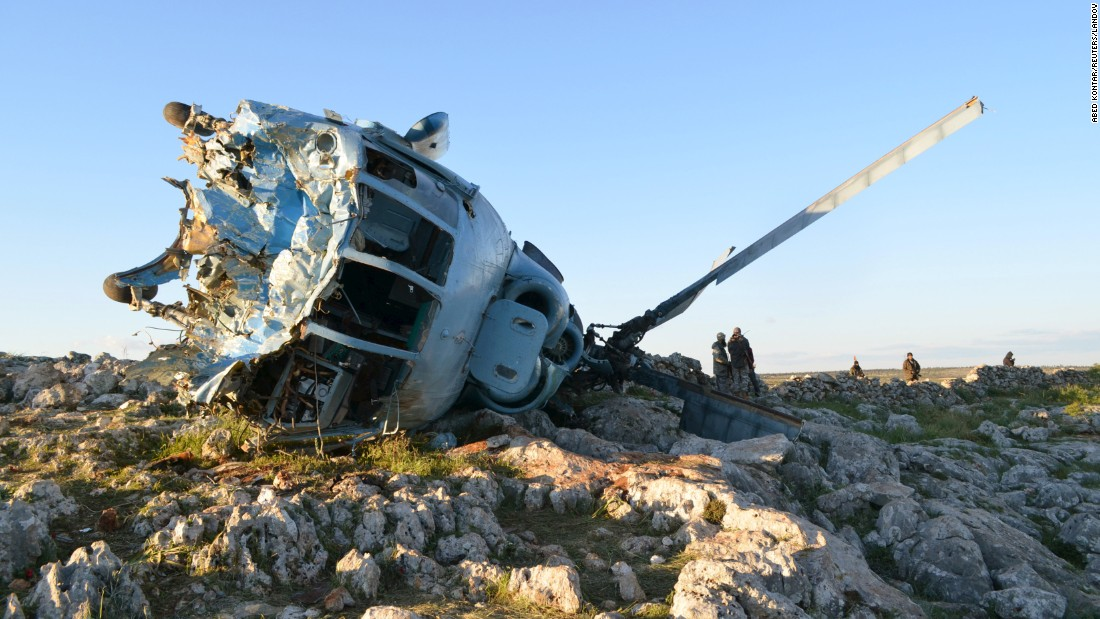 Nusra Front fighters inspect a helicopter belonging to pro-government forces after it crashed in the rebel-held Idlib countryside on March 22, 2015.