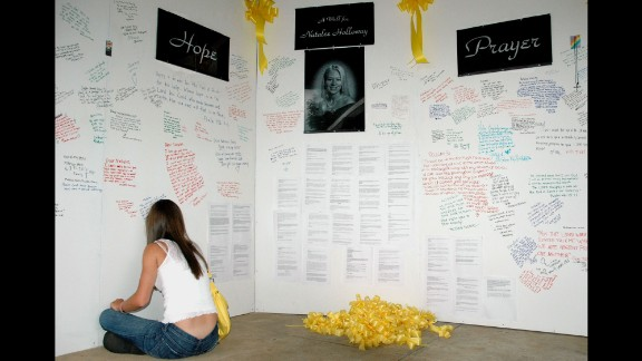 """A friend of Natalee Holloway signs a """"wall of hope"""" erected in the weeks after the Alabama teen went missing. Media from all around the world covered Holloway's disappearance."""