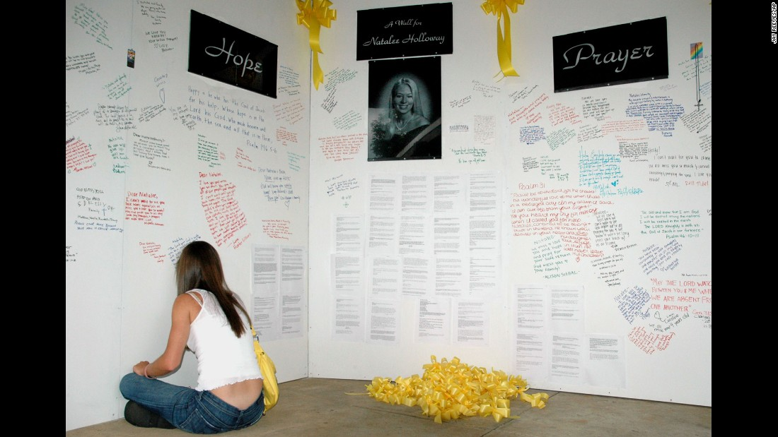 "A friend of Natalee Holloway signs a ""wall of hope"" erected in the weeks after the Alabama teen went missing. Media from all around the world covered Holloway's disappearance."