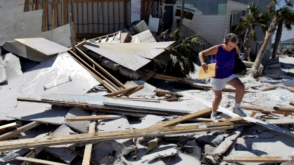 Ivan, 2004: This year also was hurricane-heavy, punctuated by Ivan, a storm with two lives. First, it killed dozens in the Caribbean and  slammed into Alabama. Later, its remnants went back over Florida from the Atlantic and re-formed in the Gulf as a tropical storm, making another landfall in southwestern Louisiana. It spawned more than 100 tornadoes, one of the factors that left considerable damage across the Southeast and some mid-Atlantic states. Here, a woman walks over debris as she visits her home, destroyed by Ivan, in Perdido Key, Florida, on September 20.