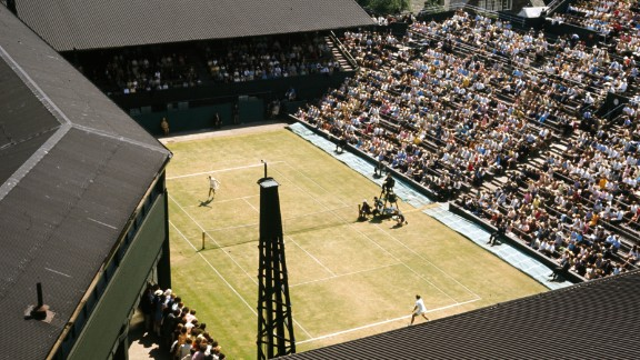 A general view of a match in progress on the Number One Court at Wimbledon in 1970. Centre Court's roofline can be seen to the left.