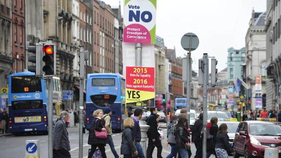 Pesdestrians cross a street next to placards on the same-sex marriage referendum in Dublin, Ireland, on May 22.