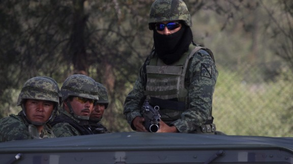 Mexican soldiers stand guard at the ranch where gunmen took cover during an intense gun battle with the police, along the Jalisco-Michoacan highway in Vista Hermosa, Michoacan State, on May 22, 2015. At least 37 people were killed in the gunfight in Mexico