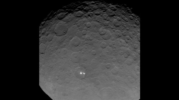 """Dawn gave scientists a big surprise: Ceres has a group of bright spots glowing inside a large crater. The above image is part of a sequence taken by Dawn on May 16, 2015 when the spacecraft was 4,500 miles (7,200 kilometers) away from Ceres. It's the closest view yet of the spots. But what are they? According to the mission's principal investigator, Christopher Russell, scientists have concluded the spots are """"due to the reflection of sunlight by highly reflective material on the surface, possibly ice."""""""