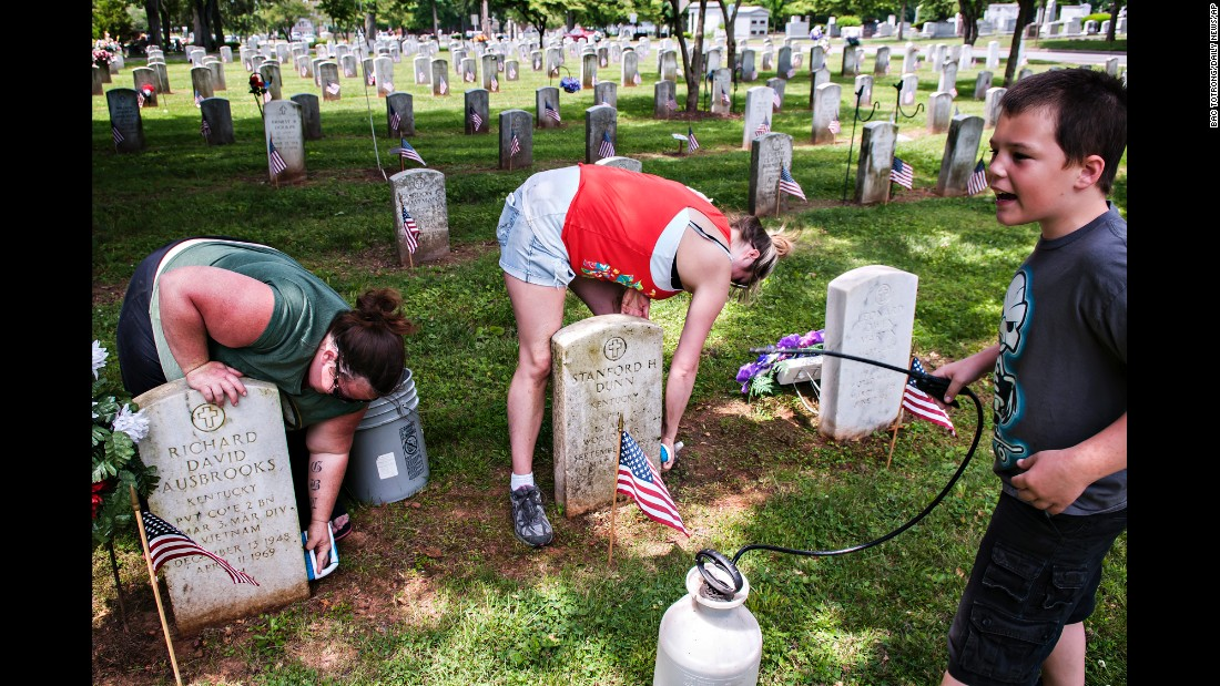 From left, Carla Lawrence, her sister Brandi Burch and her son Gabe Lawrence clean veterans' gravestones at Fairview Cemetery in Bowling Green, Kentucky, on Sunday, May 24. Burch's grandfather, great-grandfather, and great-great-grandfather are all buried at the cemetery.