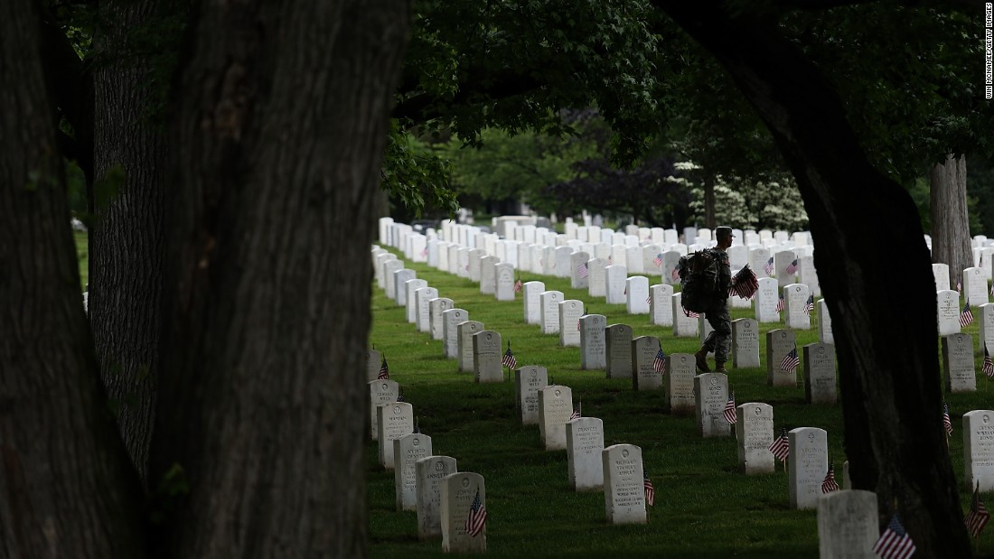 Members of the 3rd U.S. Infantry Regiment place American flags at the foot of graves in Arlington National Cemetery on Thursday, May 21.