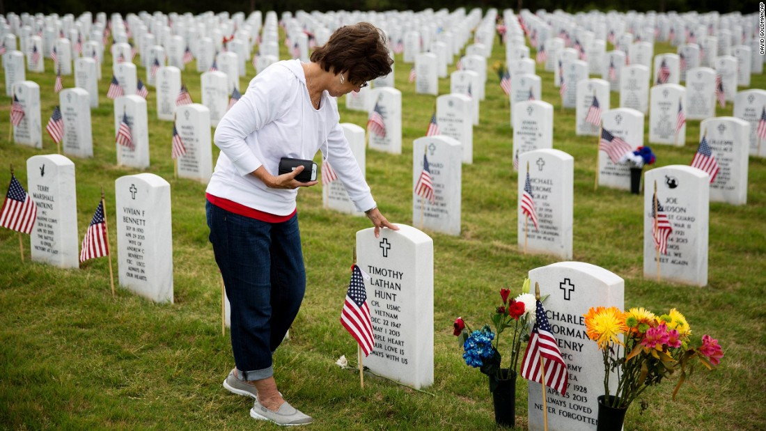 "Vickie Hunt touches the tombstone of her late husband, Vietnam veteran Timothy Hunt, while visiting Georgia National Cemetery in Canton, Georgia, on Monday, May 25. ""I come every Memorial Day,"" Hunt said. ""As soon as I go through the gates here it brings me a sense of peace."""