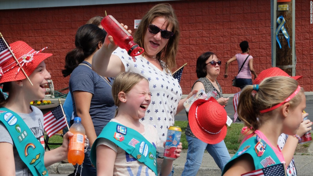 A young Girl Scout laughs while getting cooled off during a parade in Washingtonville, New York, on May 25.