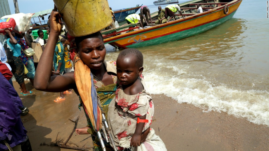 A mother carries her child ashore in Kigoma.