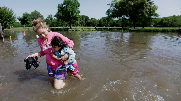 Nayeli Cervantes carries her friend's daughter through the floodwaters outside their Houston apartment on May 26.