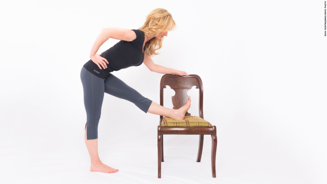 While holding your chair back or desk for balance, place your left foot on the seat of your chair. If necessary, lower your chair height to a safe, comfortable level. Keep your hips squared and your left toes in dorsi flexion (pointing up). Exhale as you flex from your hips — as opposed to rounding your back — to bend forward toward your leg. Hold for three long, deep breaths. Repeat on the other side.